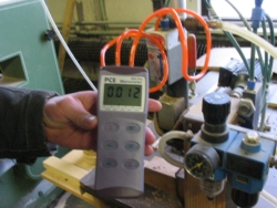 The PCE-P15 Differential Pressure Meter measuring differential pressure of a machine's motor